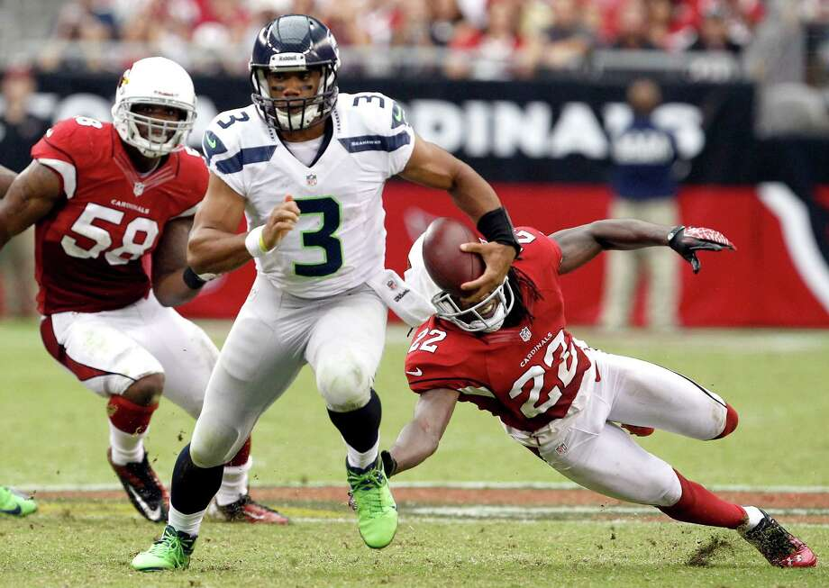 Seattle Seahawks' Russell Wilson (3) gets past Arizona Cardinals' Daryl Washington (58) and William Gay (22) during the second half in an NFL football game Sunday, Sept. 9, 2012, in Glendale, Ariz.  The Cardinals defeated the Seahawks 20-16. Photo: AP