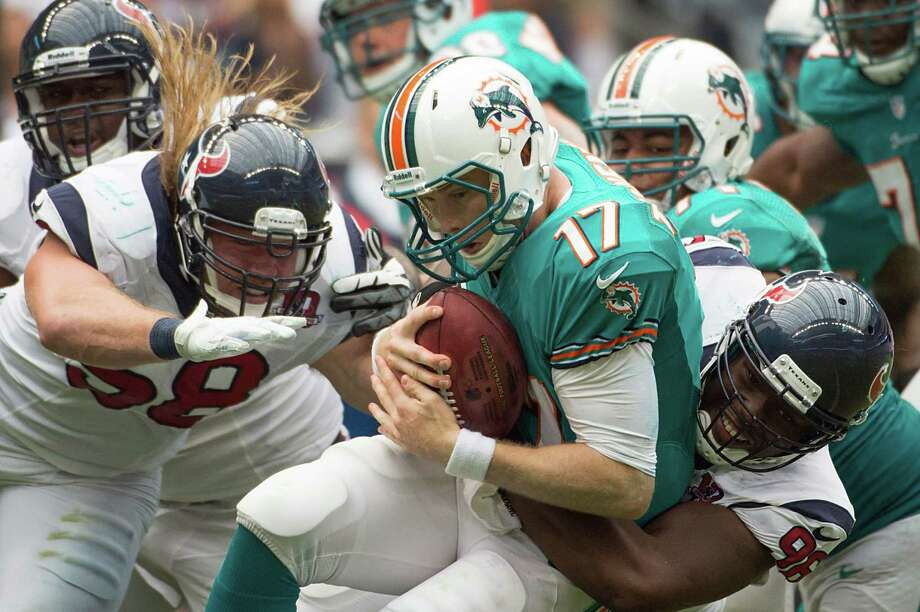 Dolphins rookie Ryan Tannehill (17) is sacked by Texans defensive end Tim Jamison in the fourth quarter Sunday. The Texans got to the former Texas A&M quarterback three times, and he admitted the speed of the game picks up relative to practice. Photo: Smiley N. Pool / © 2012  Houston Chronicle