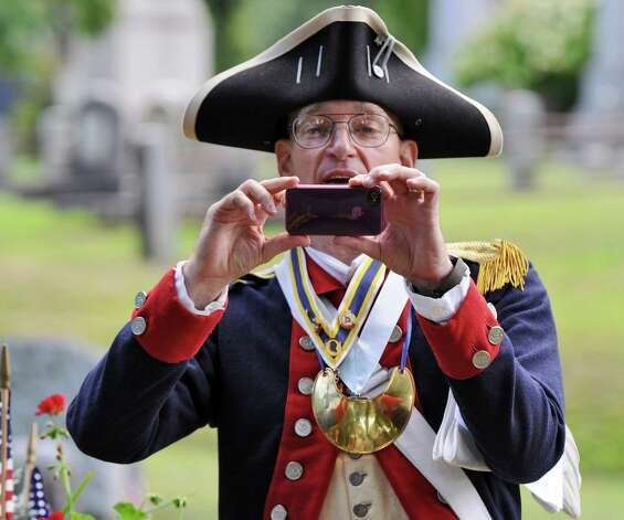 Peter Goebel of North Nassau, dressed as a Revolutionary War Colonel, and a member of the Sons of the American Revolution, takes a picture with a cell phone during a rededication of the Uncle Sam burial site at Oakwood Cemetery, by the NYS Organization of the Daughters of the American Revolution, on Sunday Sept. 9, 2012 in Troy, NY.  Goebel just retired as a Colonel after serving 30 years in the US Army.   (Philip Kamrass / Times Union) Photo: Philip Kamrass / 00019171A