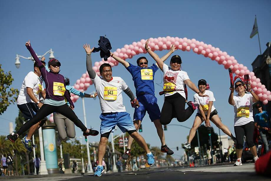 Members of the Philippine Consulate jump after they cross the finish line in the Komen San Francisco Bay Area Race for the Cure, the annual 5-kilometer run and walk that raises money for breast cancer research. Photo: Alex Washburn, Special To The Chronicle