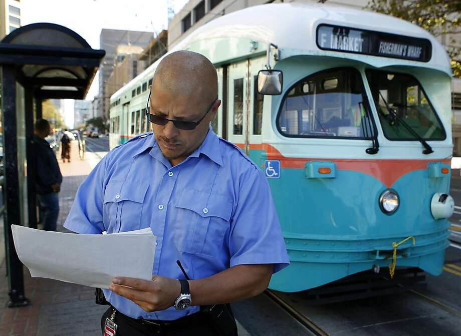 Muni street inspector Marcus Marcic logs the arrival time of an F-Market streetcar. Photo: Paul Chinn, The Chronicle