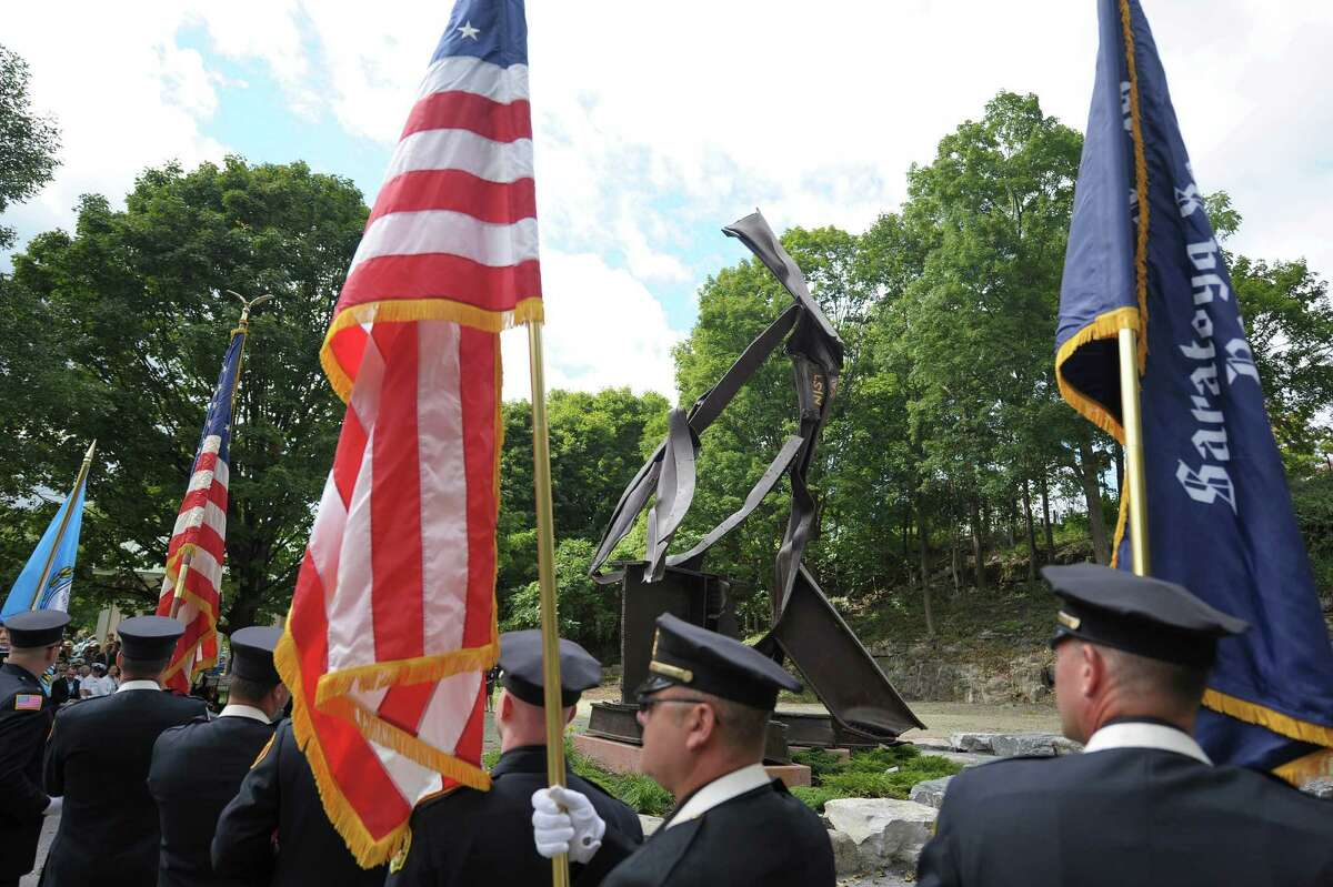 Saratoga Springs firefighters and police officers march in pasts the 9/11 sculpture during a dedication ceremony for the sculpture entitled