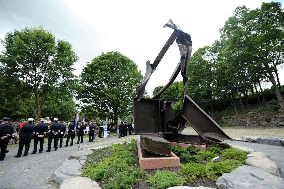Saratoga Springs firefighters and police officers stand stand at parade rest as visitors look on during a dedication ceremony for the 9/11 sculpture entitled