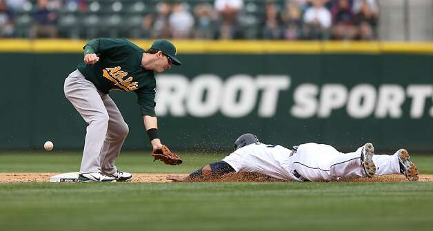 SEATTLE, WA - SEPTEMBER 09:  The throw gets by shortstop Stephen Drew #5 of the Oakland Athletics on a steal by Miguel Olivo #30 of the Seattle Mariners at Safeco Field on September 9, 2012 in Seattle, Washington.  (Photo by Otto Greule Jr/Getty Images) Photo: Otto Greule Jr, Getty Images