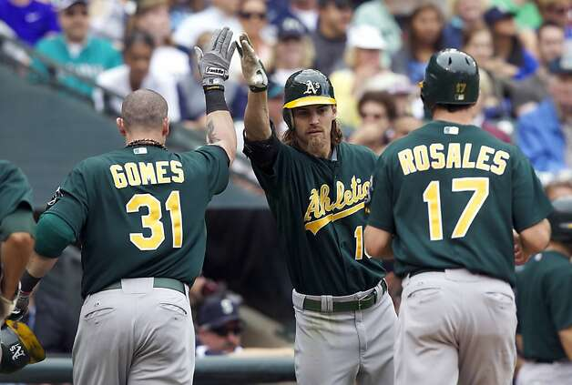 Oakland Athletics' Josh Reddick, center, congratulates teammate Jonny Gomes, left, after Gomes hit a three-run home run in the fifth inning of a baseball game against the Seattle Mariners at Safeco Field in Seattle, Sunday, Sept 9, 2012. Athletics' Adam Rosales, right, who also scored, looks on. (AP Photo/Stephen Brashear) Photo: Stephen Brashear, Associated Press