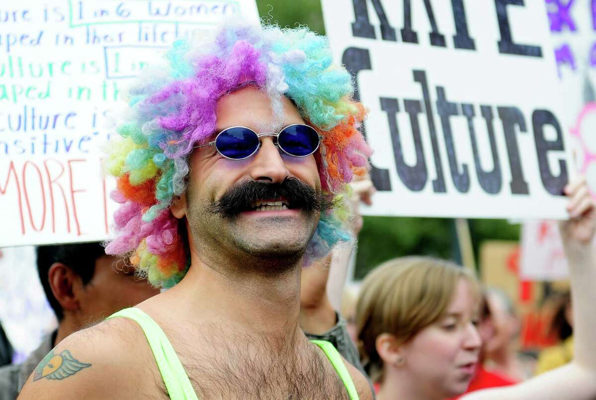 A man in a rainbow wig smiles as he marches.