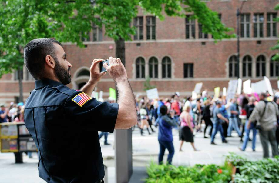 A security guard takes a photo of the scene as Seattle SlutWalk 2012 approaches the Seattle Central Library on Fourth Avenue. Photo: LINDSEY WASSON / SEATTLEPI.COM