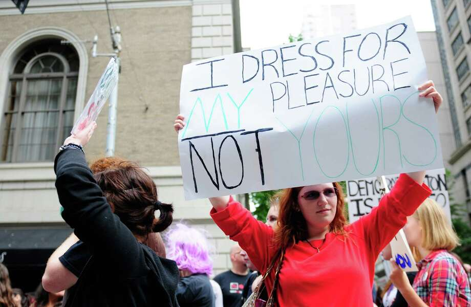 A woman holds up a sign defending her clothing choices. Photo: LINDSEY WASSON / SEATTLEPI.COM