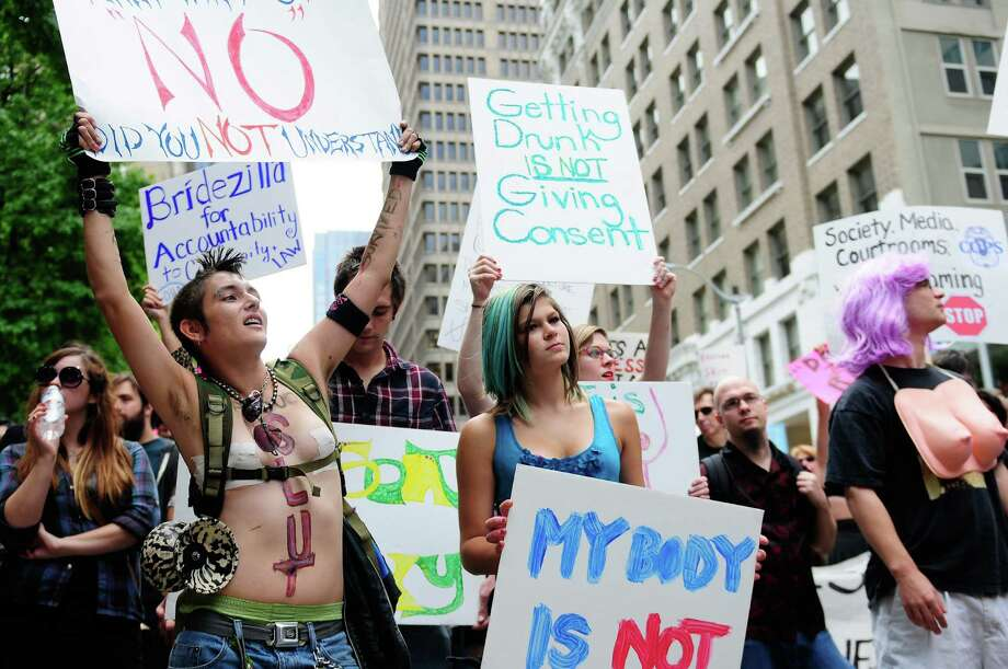 Many women hold up signs as they march to Westlake Center. Photo: LINDSEY WASSON / SEATTLEPI.COM