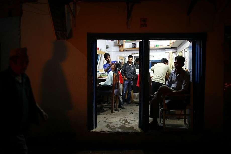 A man gets a hair cut as others look on in Katmandu, Nepal, Sunday, Sept. 9, 2012. (AP Photo/Niranjan Shrestha) Photo: Niranjan Shrestha, Associated Press