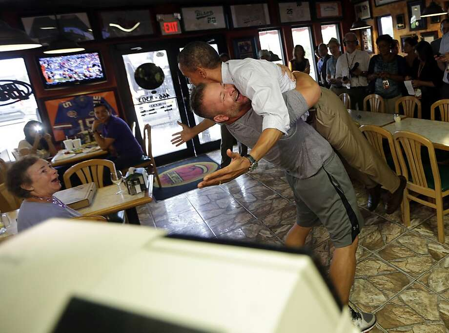 President Barack Obama, right, is picked-up and lifted off the ground by Scott Van Duzer, left, owner of Big Apple Pizza and Pasta Italian Restaurant during an unannounced stop, Sunday, Sept. 9, 2012, in Ft. Pierce, Fla. (AP Photo/Pablo Martinez Monsivais) Photo: Pablo Martinez Monsivais, Associated Press