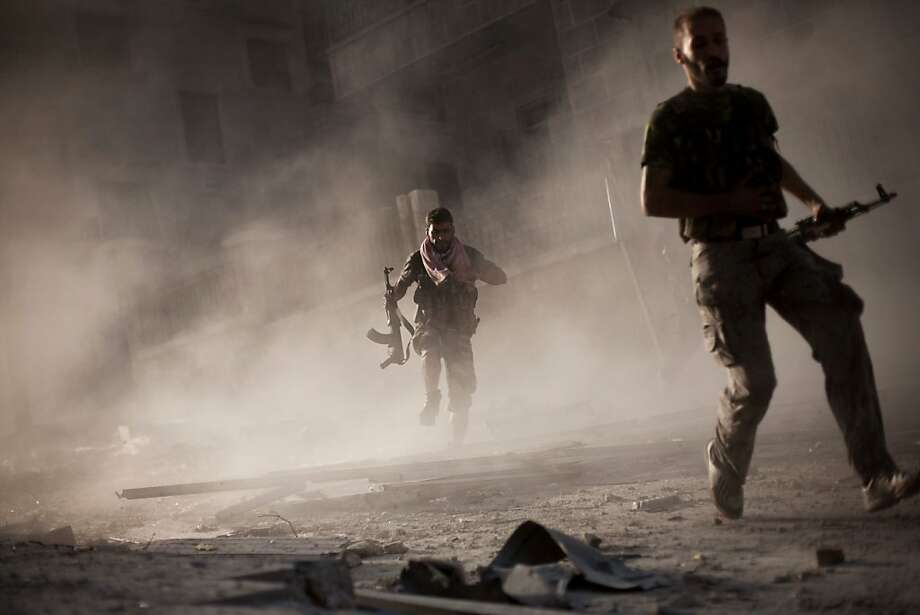 In this Friday, Sept 7, 2012 photo, Two rebel Free Syrian Army soldiers run after attacking a Syrian Army tank during fighting in the Izaa district in Aleppo, Syria.  On Friday, U.S. Senators John McCain, Joe Lieberman and Lindsay Graham, who have toured the volatile Middle East in recent days, urged Washington to help arm Syria's rebels with weapons and create a safe zone inside the country for a transition government. (AP Photo/ Manu Brabo) Photo: Manu Brabo, Associated Press