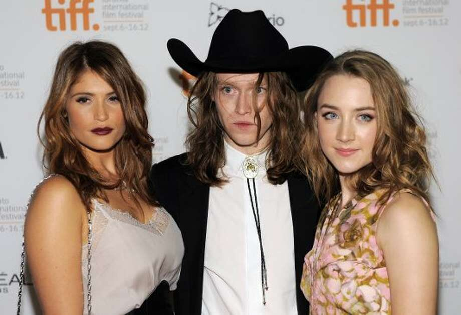 "Gemma Arterton, left, Caleb Landry Jones, center, and Saoirse Ronan, cast members in the film ""Byzantium,"" pose together at the premiere of the film. (CHRIS PIZZELLO/INVISION/AP)"