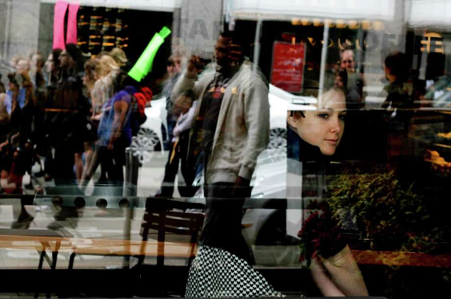 Kenna Stout looks out of a window as protesters walk by. Photo: Sofia Jaramillo / SEATTLEPI.COM