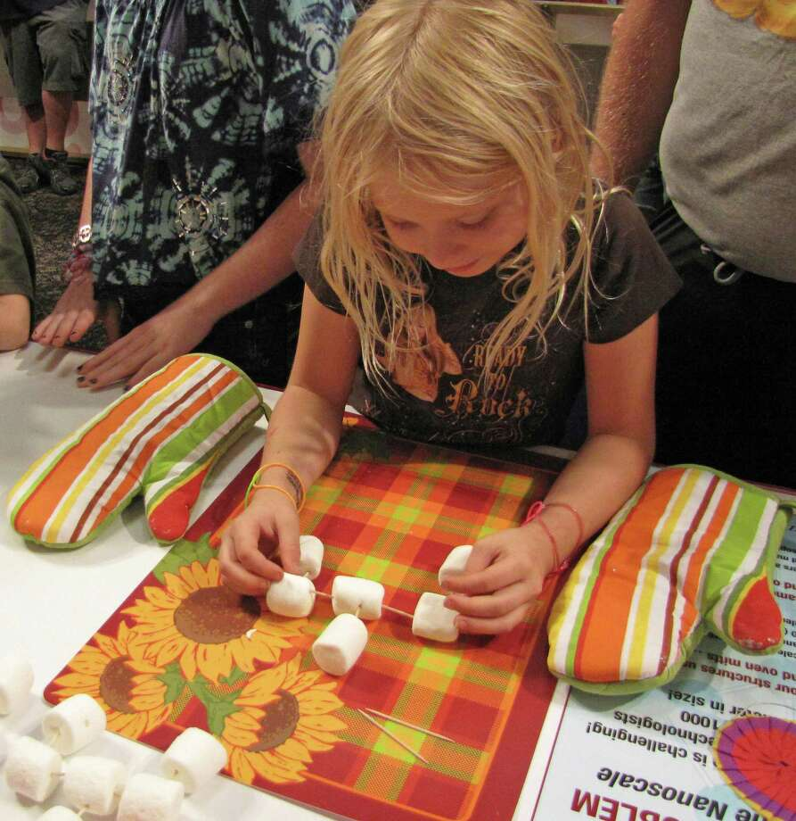 "Samantha Billings, a 4th grader from Harmony Hill Elementary School in Cohoes, makes a ""marshmallow molecule"" at the Questar III BOCES booth. Were you Seen at the Back to School Expo at Empire State Plaza on Saturday, Sept. 8, 2012? Photo: Anne-Marie Sheehan"