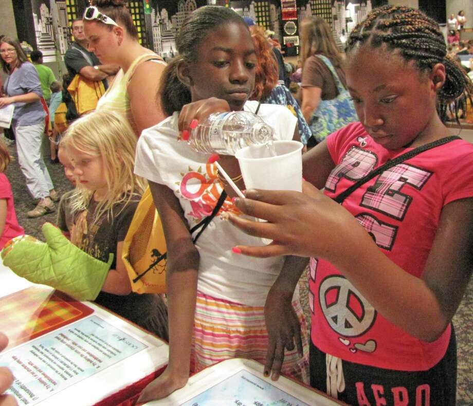"Nijhera Johnson, a 6th grader from Albany, learns about ""slime polymers"" at the Questar III BOCES booth. Were you Seen at the Back to School Expo at Empire State Plaza on Saturday, Sept. 8, 2012? Photo: Anne-Marie Sheehan"