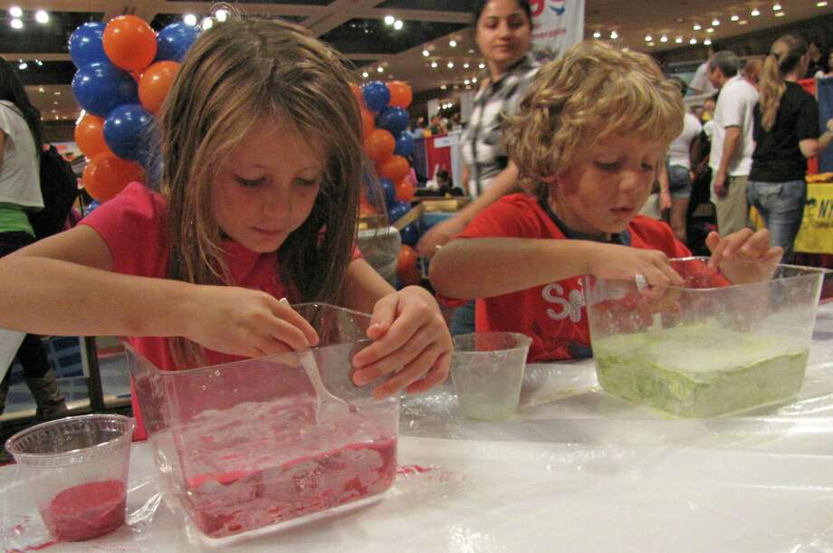 "Jeana Montalbano, a kindergartner at Lynwood Elementary School in Guilderland, and her brother, Joey, learn about ""magic sand"" an oil-like substance that repels water. 2012 Back to School Expo at the Empire State Plaza. Photo by Anne-Marie Sheehan. Photo: Anne-Marie Sheehan"