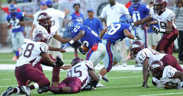 "West Brook ball runner #25, Justin Hervey, looks for a hole to go through the Central defense. The Central Medical Magnet High School football team played West Brook High School Friday night in the second Beaumont Bowl match up at the Carrol A. ""Butch Thomas Educational Support Center.  Both teams entered the Friday September 7 matchup with o-1 records.  At the half, West Brook was ahead 20-7. Dave Ryan/The Enterprise Photo: Dave Ryan"