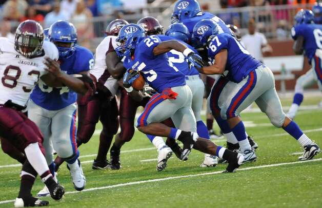 "West Brook ball carrier #25, Justin Hervey, center, heads for a hole opened up by his teammates. The Central Medical Magnet High School football team played West Brook High School Friday night in the second Beaumont Bowl match up at the Carrol A. ""Butch Thomas Educational Support Center.  Both teams entered the Friday September 7 matchup with o-1 records.  At the half, West Brook was ahead 20-7. Dave Ryan/The Enterprise Photo: Dave Ryan"