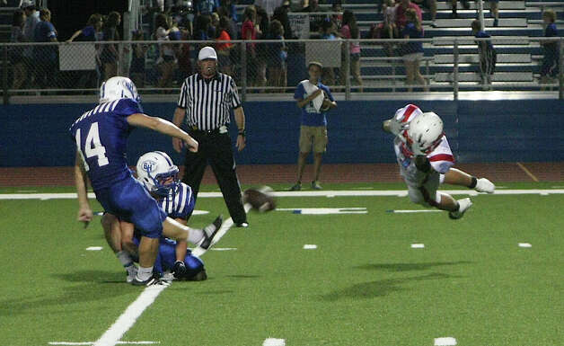 Dustin Ford attempts to block one of many PAT attempts by Barbers Hill during the Raider loss Friday night. Photo: David Lisenby, Freelance