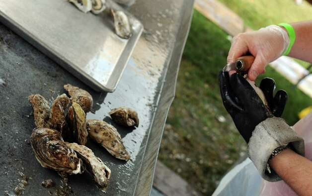 Alan Schleier shucks oysters at the 35th annual norwalk Oyster Festival at Veteran's Park on Saturday, September 8, 2012. Photo: Lindsay Niegelberg / Stamford Advocate