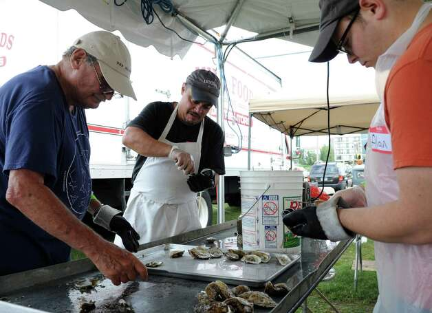 From left, Howard Schleier, Joe Madaffari, and Alan Schleier shuck oysters at the 35th annual norwalk Oyster Festival at Veteran's Park on Saturday, September 8, 2012. Photo: Lindsay Niegelberg / Stamford Advocate