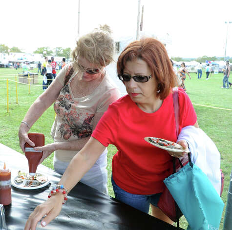 Louise Carbonaro, left, and Georgette Spindler, right, put cocktail sauce on their oysters at the 35th annual norwalk Oyster Festival at Veteran's Park on Saturday, September 8, 2012. Photo: Lindsay Niegelberg / Stamford Advocate