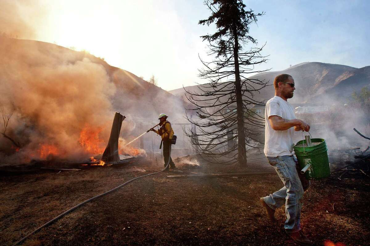 A North Kitsap County firefighter battles a blaze in a shed as owner Mickey Daniels moves a bucket of sand away from the flames Sunday, Sept. 9, 2012, in Wenatchee, Wash. Daniels' home was at the edge of a large lightning strike ignited brush fire that crept close to many houses.