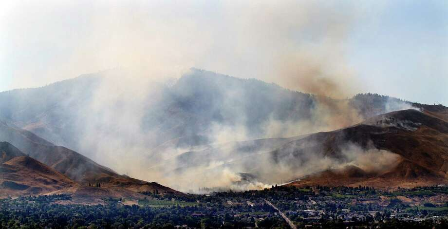 A brush fire burns into Number 1 Canyon west of Wenatchee, Wash., Sunday, Sept. 9, 2012, in a view looking west from East Wenatchee. Overnight lightning strikes sparked dozens of new fires in Washington state. Photo: Don Seabrook / The Wenatchee World via AP