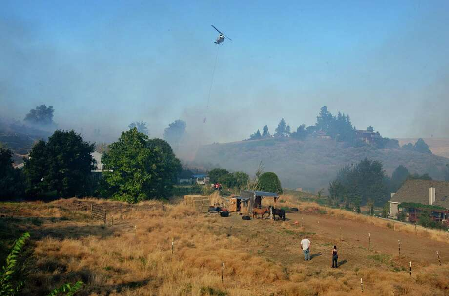 A helicopter dumps water on a fire near houses on Sage Hills Drive just west of Wenatchee, Wash.,  Sunday, Sept. 9, 2012, as residents watch and tend to their horses from below. Overnight lightning strikes sparked dozens of new fires in Washington state. Photo: Don Seabrook / The Wenatchee World via AP
