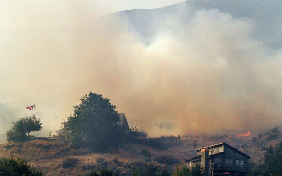 A strong wind pushes flames and smoke toward houses on Austin Court just west of Wenatchee, Wash., in a brush fire in Number 1 Canyon on Sunday afternoon, Sept. 9, 2012. Overnight lightning strikes sparked dozens of new fires in Washington state. Photo: Don Seabrook / The Wenatchee World via AP