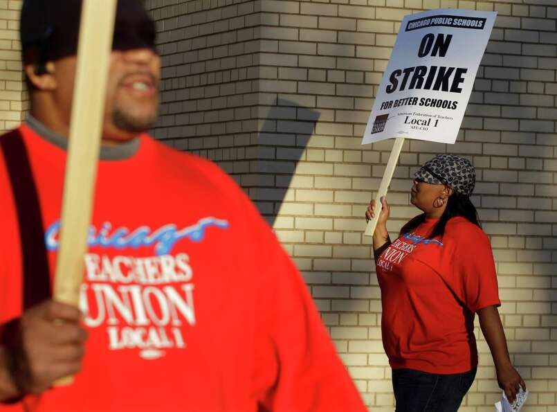 Chicago teachers Michael Williams and Alma Hill walk a picket line outside Benjamin Banneker Element