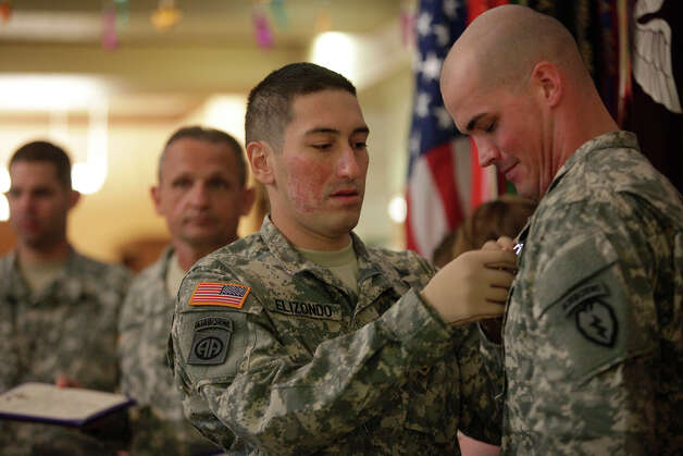 Infantryman Staff Sgt. Shaun Elizondo (left) pins the Purple Heart, after receiving his own, on the lapel of Infantryman Spec. Seth Pardue during a May ceremony at Fort Sam Houston. Both men were injured  in Afghanistan. Photo: Lisa Krantz, San Antonio Express-News / SAN ANTONIO EXPRESS-NEWS