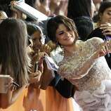 "Actress Selena Gomez takes a photo with fans as she walks the red carpet for the movie ""Spring Breakers."" (ASSOCIATED PRESS)"