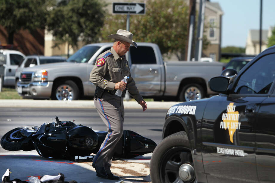 Texas Department of Public Safety troopers work at the scene of a motorcyle accident after it collided with a pickup truck (background) Monday morning September 10, 2012 near the intersection of Culebra and Reed Road. Trooper Jason Reyes said the man on the motorcycle, a Mexican national in his 20s, had been running red lights on Culebra. A chase ensued for about two miles until the man crashed on the motorcycle. The motorcyclist may have broken some bones, but did not suffer from life threatening injuries. Reyes said it was not clear why the man failed to stop for the troopers. Photo: John Davenport/San Antonio Express-News