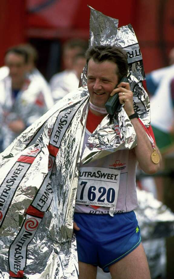 A competitor chats on his mobile phone after the Nutrasweet London Marathon on April 17, 1994. Photo: Clive Brunskill, Getty Images / Getty Images Europe