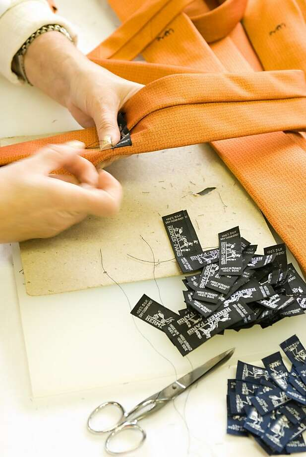An Hermès scarf, below, is arguably the company's best-known item, but all items with an Hermès tag, above, rely on craftsmanship. Photo: Hermes