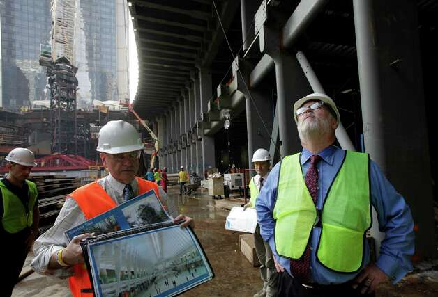 Steve Plate, left, Director of Construction for the World Trade Center, holds a folder of architectural images as he tours the transportation hub with Patrick Foye, right, Executive Director of the Port Authority of New York and New Jersey, in New York. When it opens in 2015, the station will serve 250,000 travelers a day. Photo: Mark Lennihan / Associated Press