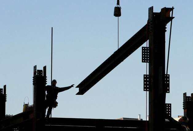 An ironworker reaches for a beam suspended from a crane at One World Trade Center, in New York. Eleven years after terrorists attacked the World Trade Center, the new World Trade Center now dominates the lower Manhattan skyline. Photo: Mark Lennihan / Associated Press