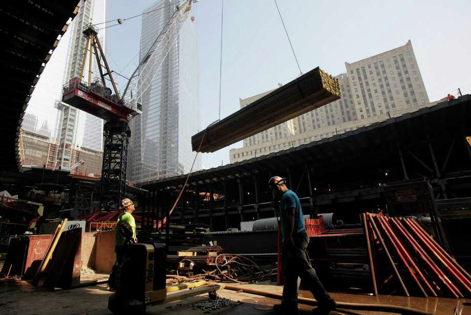 An ironworker watches as a crane lifts a load of construction supplies at the World Trade Center transportation hub, in New York. The new transportation hub at the trade center will connect 13 subway lines and PATH trains to New Jersey when it opens in 2015. Photo: Mark Lennihan / Associated Press