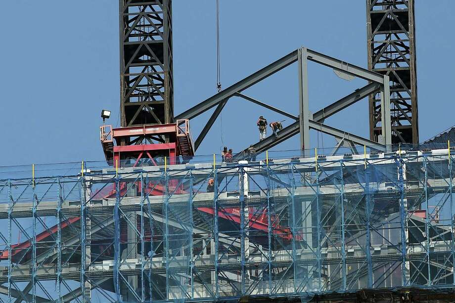 Construction workers work on One World Trade Center on September 7, 2012 in New York City. As New York City and the country prepare for the 11th anniversary of the September 11, 2001 terrorist attacks, work proceeds at the former site of the World Trade Center Towers. The 16-acre site, which is owned by the Port Authority of New York and New Jersey and is being rebuilt with developer Larry Silverstein, has a projected price tag of $14.8 billion. Of the four office towers planned for the site, two have had finishing beams placed on their top floors and the above-ground memorial was completed in time for the 10th anniversary last year. Photo: Spencer Platt / Getty Images