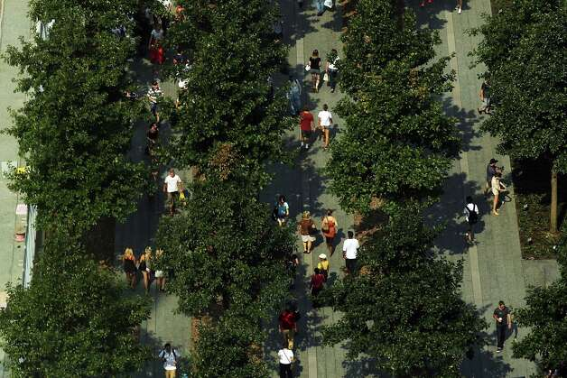 People are viewed walking at the National September 11 Memorial Museum on September 7, 2012 in New York City. As New York City and the country prepare for the 11th anniversary of the September 11, 2001 terrorist attacks, work proceeds at the former site of the World Trade Center Towers. The 16-acre site, which is owned by the Port Authority of New York and New Jersey and is being rebuilt with developer Larry Silverstein, has a projected price tag of $14.8 billion. Of the four office towers planned for the site, two have had finishing beams placed on their top floors and the above-ground memorial was completed in time for the 10th anniversary last year. Photo: Spencer Platt / Getty Images