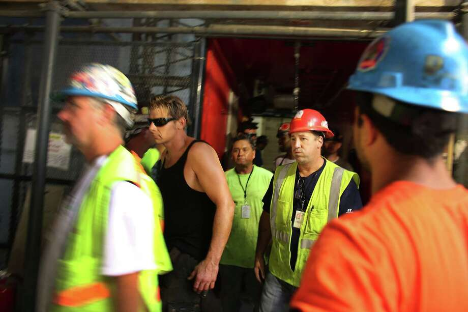 Construction workers exit a elevator down from the top floor at Four World Trade Center on  September 7, 2012 in New York City. As New York City and the country prepare for the 11th anniversary of the September 11, 2001 terrorist attacks, work proceeds at the former site of the World Trade Center Towers. The 16-acre site, which is owned by the Port Authority of New York and New Jersey and is being rebuilt with developer Larry Silverstein, has a projected price tag of $14.8 billion. Of the four office towers planned for the site, two have had finishing beams placed on their top floors and the above-ground memorial was completed in time for the 10th anniversary last year. Photo: Spencer Platt / Getty Images