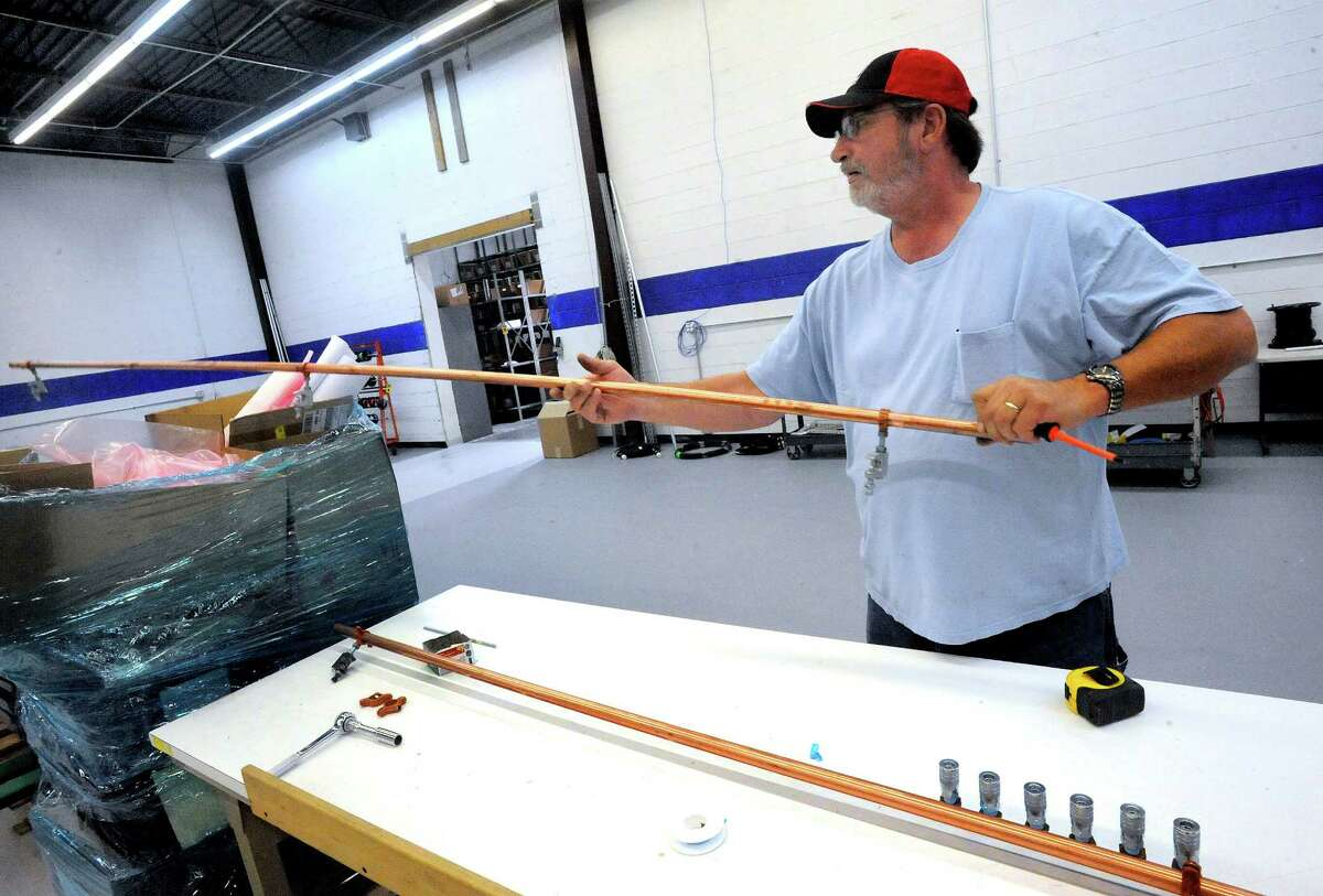 Darrel Golder mounts hangers on copper piping in Kimchuk's new System Intregration 2 facility in Danbury Monday, Sept. 10, 2012.
