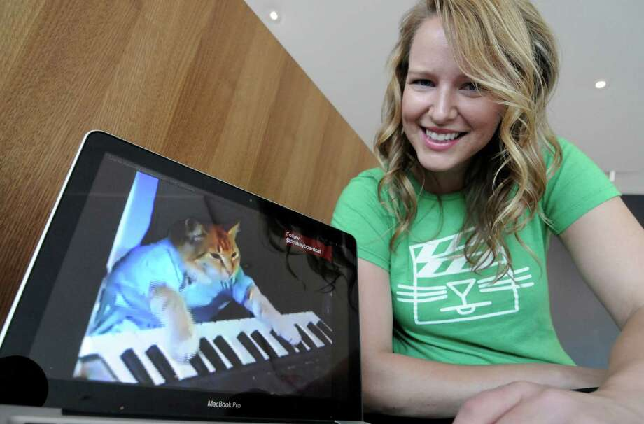 "Katie Hill, a program associate with the Walker Art Center, shows a frame from a cat video of a cat playing the piano Wednesday, Aug. 29, 2012, in Minneapolis. The Walker will present its  first ""Internet Cat Video Film Festival"" to showcase the best in filmed feline hijinks. (AP Photo/Jim Mone) Photo: Jim Mone / AP"