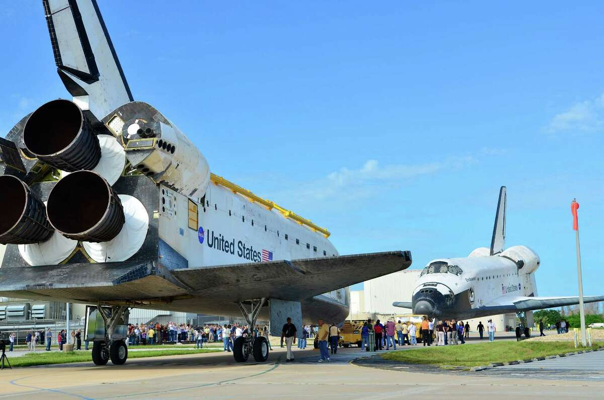 CAPE CANAVERAL, FL - AUGUST 16: Space Shuttles Atlantis (L) and Endeavour face each other as they as Endeavour backs out of the Orbiter Processing Facility and Atlantis is moved out of the Vehicle Assembly Building August 16, 2012 in Cape Canaveral, Florida. Space shuttle Endeavour will be moved to the California Science Center as a permanent exhibit and Space shuttle Atlantis will be kept at the Kennedy Space Center Visitor Complex. (Photo by Roberto Gonzalez/Getty Images)