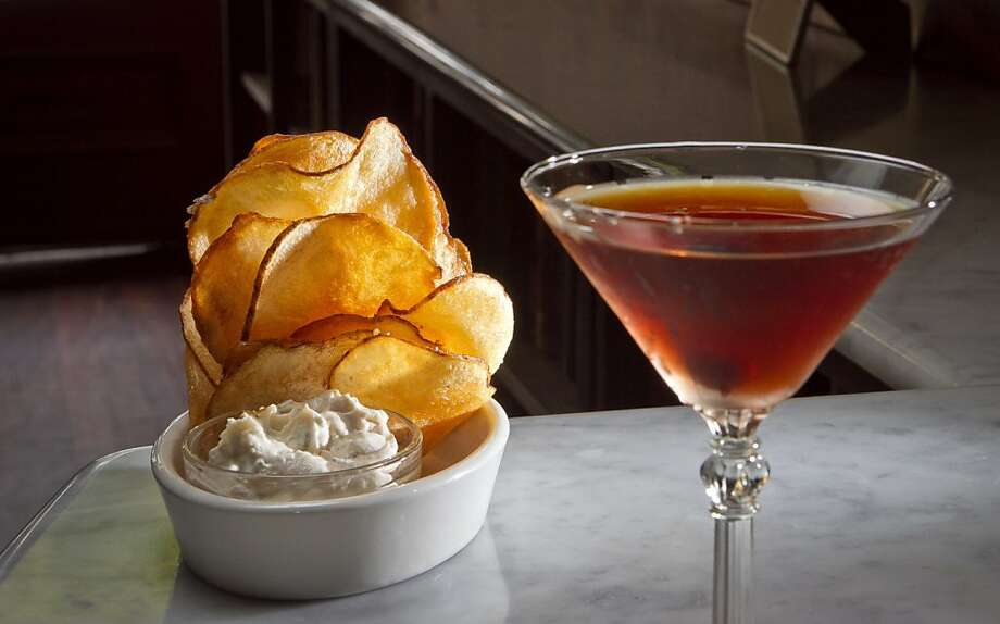 Two Sisters Bar Books, above, offers its signature cocktail and house-made potato chips. Photo: John Storey