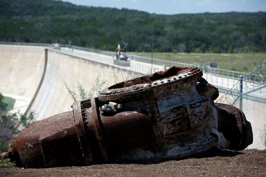 Two large pieces of equipment that appear to be two of the non-function outlet valves on the Medina Dam that were replaced during recent renovation work, are seen Thursday Sept. 6, 2012 next to the dam. Photo: William Luther, San Antonio Express-News / © 2012 San Antonio Express-News