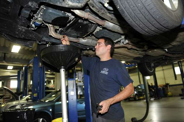 David Brusky changes the oil at Subaru of Stamford Tuesday, Sept. 4, 2012. Photo: Helen Neafsey / Greenwich Time