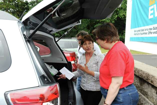 Linda Trindade, sales consultant, goes over a new car for Robert and Diane Ramirez of Greenwich, at Subaru of Stamford Tuesday, Sept. 4, 2012. Photo: Helen Neafsey / Greenwich Time